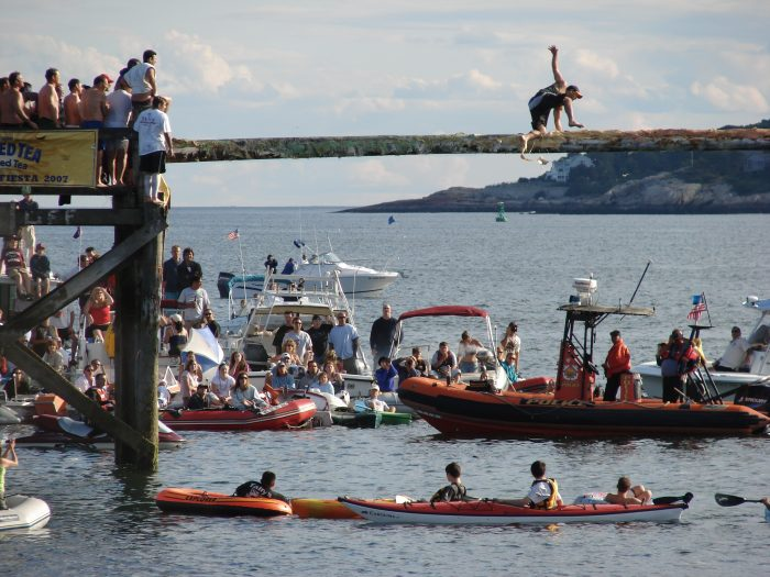 Man attempting to cross the Greasy Pole over the ocean at Saint Peter's Fiesta in Gloucester, MA